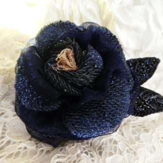 スパンコールを鱗のように刺繍した花びらを、幾重にも重ねた薔薇のブローチです。