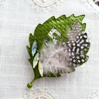 糸で畳模様に刺繍した葉っぱの形をしたブローチです。数字の5がくり抜いてあります。その周りに羽根と菱形のクリスタルが3個刺繍してあります。