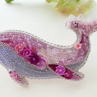 ピンク色のクジラブローチです。尻尾にはフワフワなリボンが刺繍してあります。お腹部分は光沢のある糸で流れるように刺繍してあります。スパンコールで立体的な小花が刺してあります。